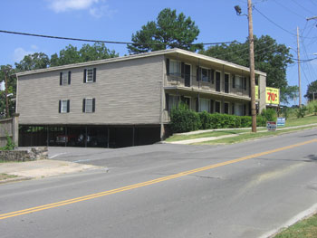 Picture of apartment building with open front and multiple doors to apartments - parking underneath building